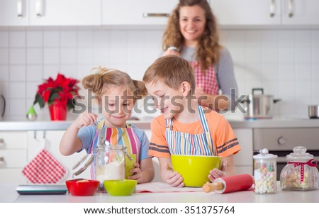 Happy family preparing cookies for Christmas eve at home - stock photo