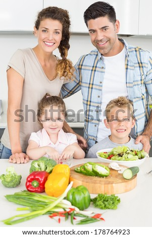 Happy family preparing vegetables together at home in kitchen