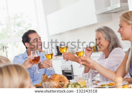 Happy family raising their glasses at thanksgiving dinner - stock photo