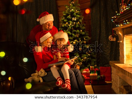 Happy family read book by Christmas tree in cozy living room front of fireplace - stock photo