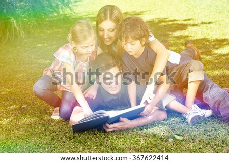 Happy family reading a book in garden in summer - stock photo