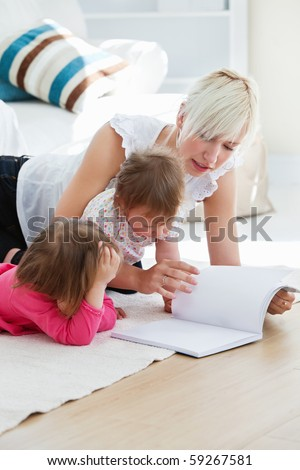 Happy family reading a book on the floor in the living-room - stock photo
