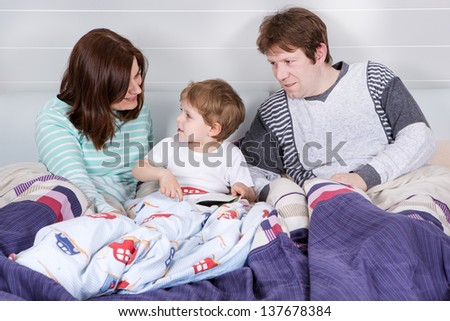 Happy family reading book before going to bed - stock photo