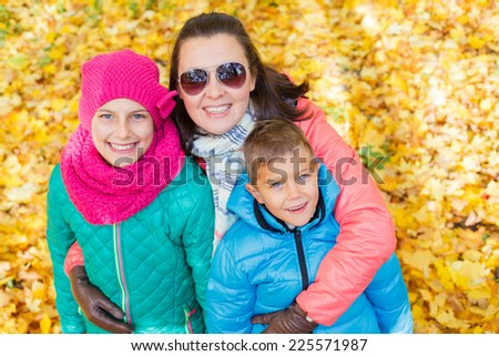 Happy family relaxing in autumn park - mother with her kids has fun in park.