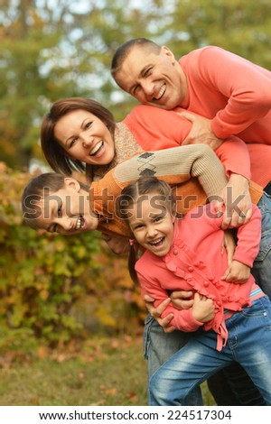 Happy family relaxing in autumn park together - stock photo