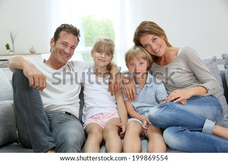 Happy family relaxing on couch at home - stock photo