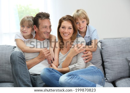 Happy family relaxing on couch at home