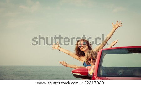 Happy family relaxing on the beach. Woman and child having fun in red cabriolet against blue sky background. Summer vacation and travel concept - stock photo