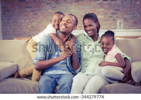 Happy family relaxing on the couch in living room - stock photo