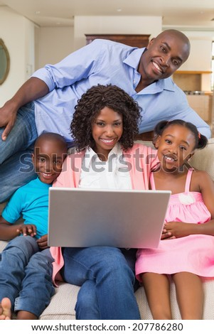 Happy family relaxing on the couch using laptop at home in the living room