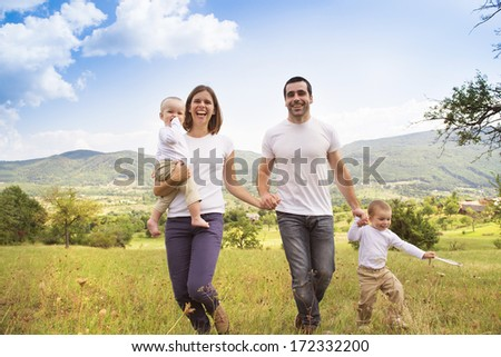 Happy family relaxing together in green nature - stock photo