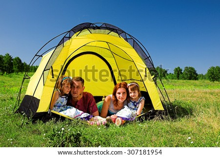 Happy family resting in the tent
