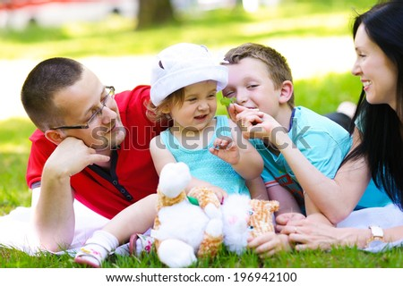 Happy family resting on the lawn in summer park - stock photo
