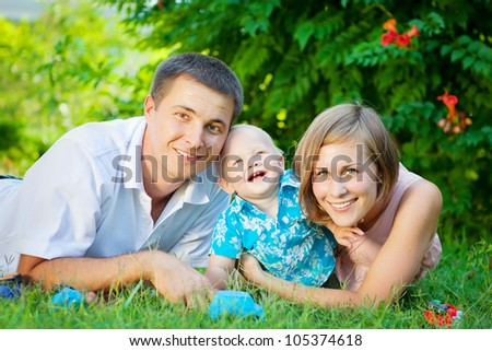 Happy family resting outdoors in summer - stock photo