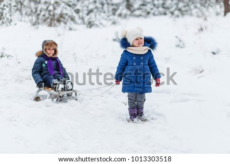 Happy family rides the sledge in the winter wood or forest, cheerful entertainments, everything is covered with snow around. A small boy and girl in the park outdoors playing with  snow