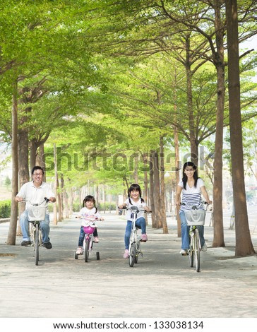 happy family riding bicycle in the park - stock photo