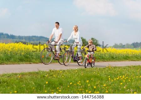 happy family riding bikes in green landscape - stock photo