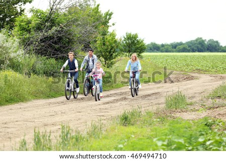 Happy family riding bikes on country road