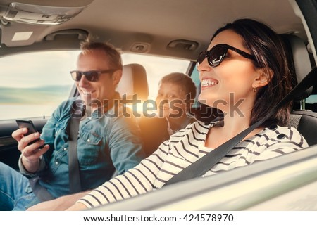 Happy family riding in a car - stock photo