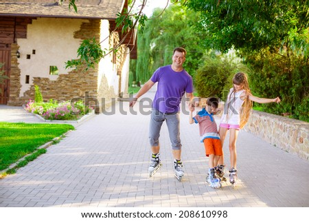 happy family riding rollerblading on a summer day - stock photo