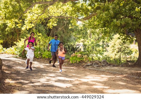Happy family runing together in a park