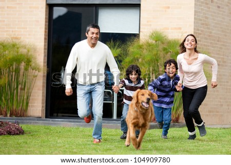 Happy family running after a dog outdoors - stock photo