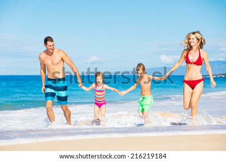 Happy Family Running and Playing on the Beach - stock photo