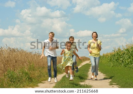 Happy family running on a dirt road - stock photo