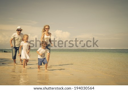 Happy family running on the beach at the day time - stock photo