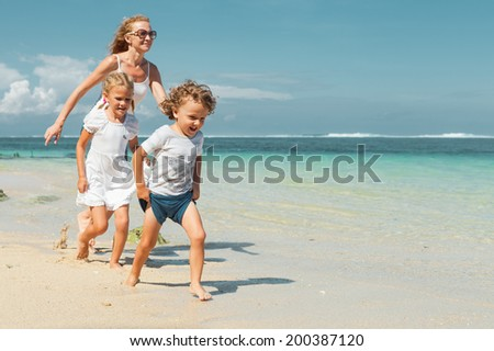 Happy family running on the beach at the day time