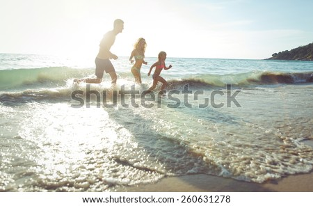 happy family running out the water in kata beach. concept about vacations and family - stock photo