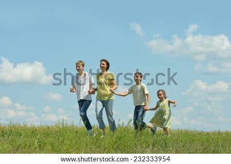 Happy family running outdoors against the sky