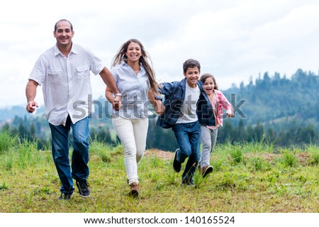Happy family running outdoors in the countryside - stock photo
