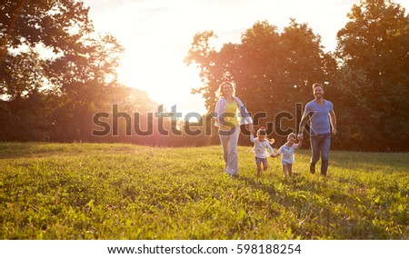 Happy family running together in park