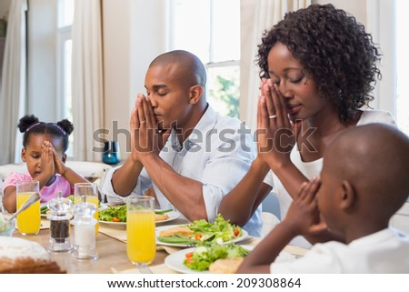 Happy family saying grace before meal at home in the kitchen - stock photo