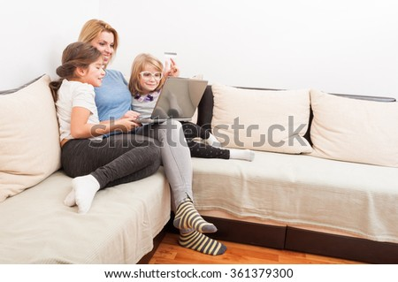 Happy family shopping online concept using laptop and credit or debit card