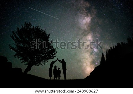 Happy family silhouette with Milky Way and beautiful night sky full of stars in background making house shape for care and love concept