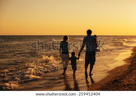 happy family silhouettes on beach at sunset