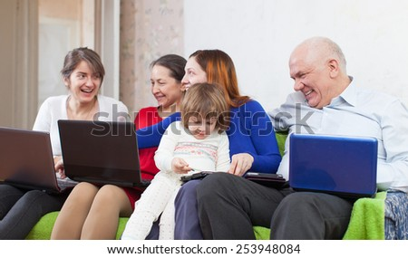 Happy family sits  in livingroom with few laptops at home - stock photo