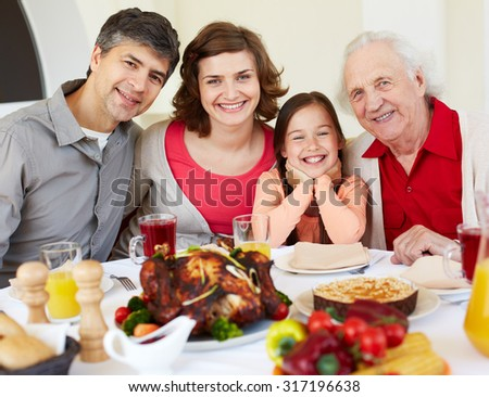 Happy family sitting at celebration table on Thanksgiving Day - stock photo