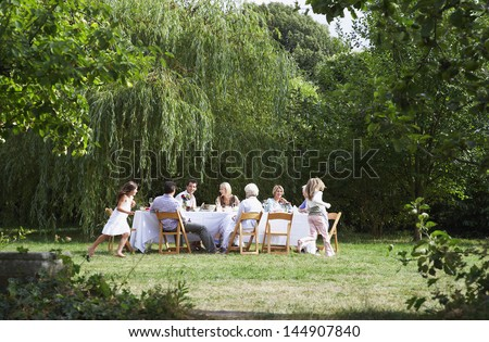 Happy family sitting at dining table while girls running around in garden - stock photo