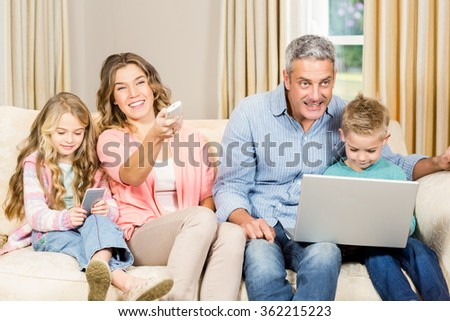 Happy family sitting at home using remote and a laptop