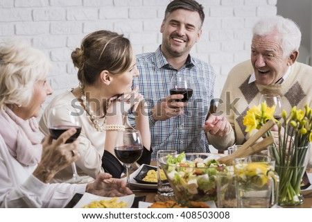 Happy family sitting beside table during dinner, smiling - stock photo