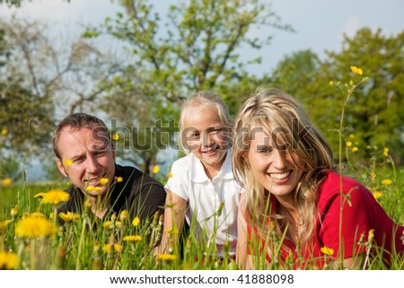 Happy family sitting in a meadow full of dandelions in spring (selective focus on girl) - stock photo