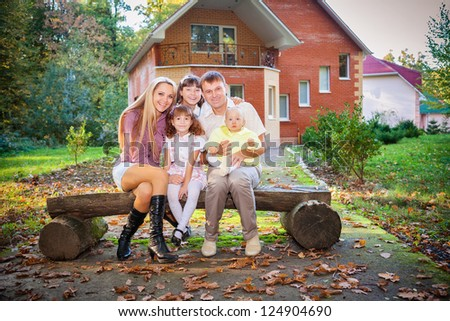 happy family sitting in backyard of new home - stock photo