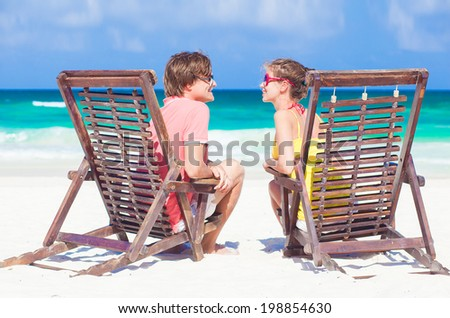 happy family sitting in chairs at the beach - stock photo