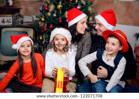 Happy family sitting in front of christmas tree. Celebrating Christmas. - stock photo
