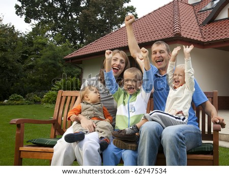 Happy family sitting in front of the house - stock photo