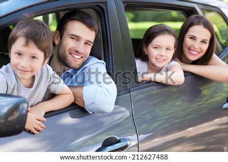 Happy family sitting in the car - stock photo