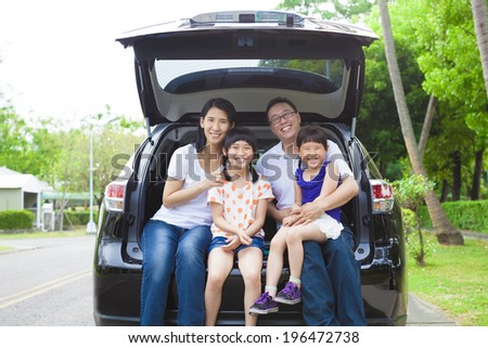 happy family sitting in the car and their house behind - stock photo